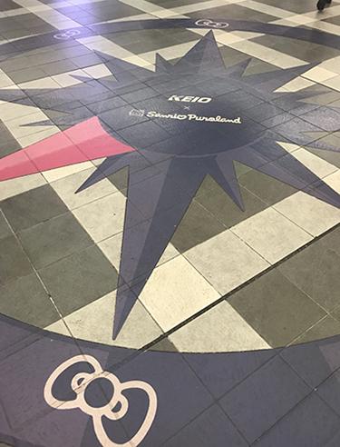 改札外の床に描かれた方位表示。キティのリボンが描いてある方向がピューロランド。